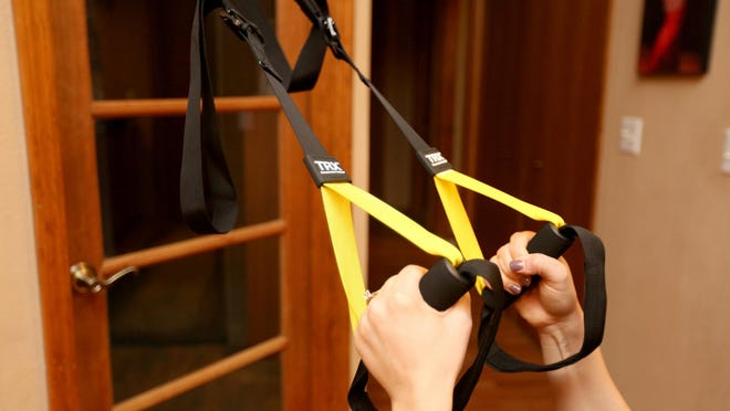 Ana Davey demonstrates a TRX row using a door frame in her living room.