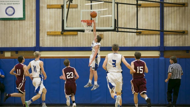 Amity senior Jamie Stull grabs the rim as he scores a basket against Dayton at a game at Amity High School on Friday, Jan. 29, 2016. Amity won 81-58.