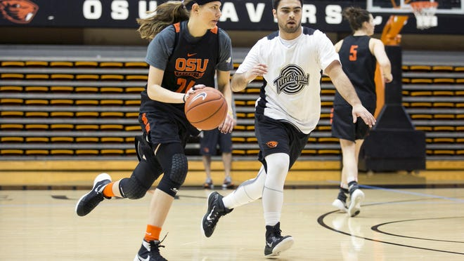 Oregon State junior Sydney Wiese dribbles around Oregon State student Roderick Phillips at a women's team practice on Thursday, Feb. 10, 2016. Phillips is a member of Tune Squad, a small group of male OSU students who practice with the women's basketball team roughly two to three times a week.