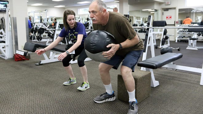 Trainer Anna Courtney coaches Rick Ricketts on his squat technique during a senior fitness class at Courthouse Athletic Club.