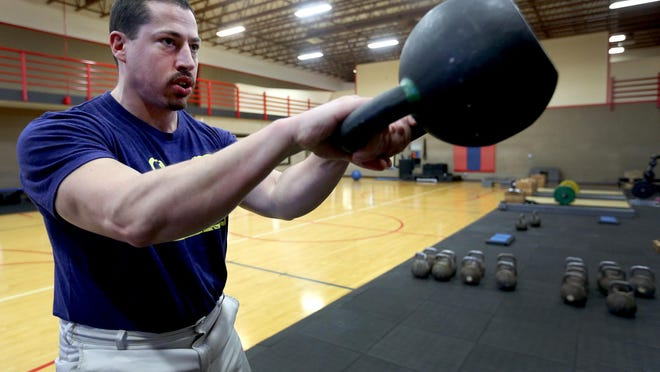 Sam McLean, a StrongFirst certified trainer, swings a kettlebell at Courthouse Athletic Club in South Salem.