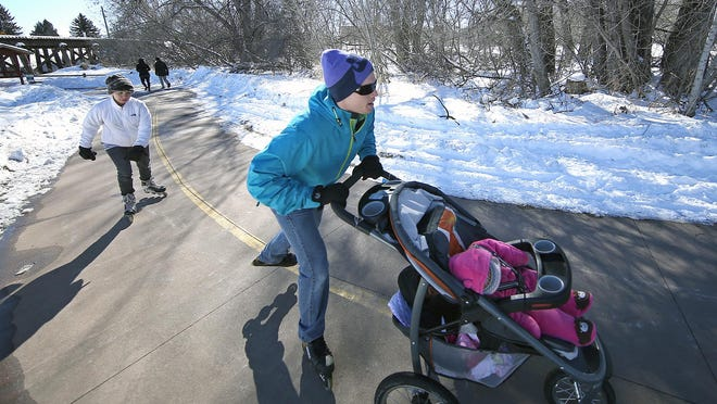 People enjoy a break from the winter weather on the Poudre Trail near Old Town Fort Collins in February.