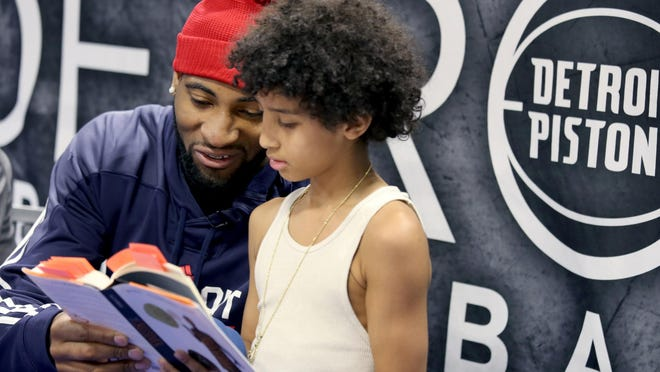 Pistons star center Andre Drummond leans in as Jose Feliciano, 12, of Detroit reads a passage.