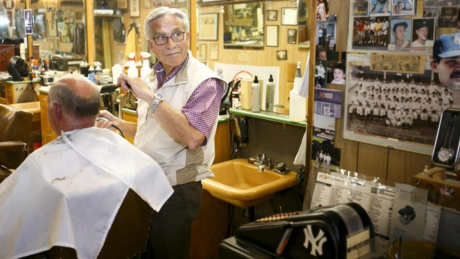 Mike Witenberger cuts hair in the his barbershop, OK Barber Shop, which is filled with baseball memorabilia. He was the first person through the turnstiles at Volcanoes Stadium on opening day in 1997.