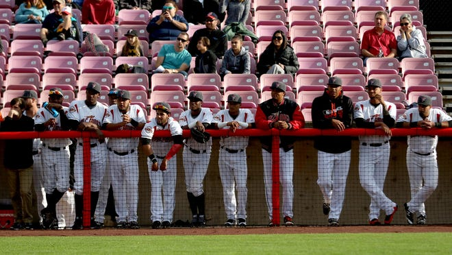 Volcanoes players watch the opening ceremonies before the 20th anniversary season opener for Volcanoes baseball at Volcanoes Stadium in Keizer on Friday, June 17, 2016.