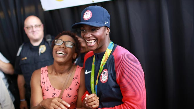 Leilani Calay of Flint laughs with back-to-back Olympic gold medalist Claressa Shields while taking a photo with her after Shields was greeted by family and fans at Flint Bishop International Airport on Tuesday.
