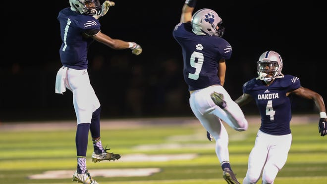 Macomb Dakota players celebrate a fumble recovery during the second half of the 35-28 win over Orchard Lake St. Mary's on Thursday at Dakota.