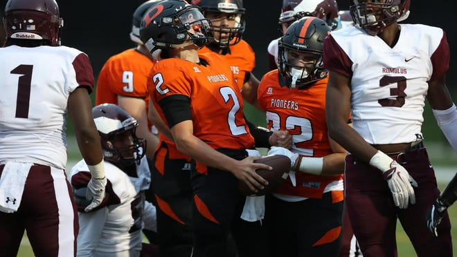 Dearborn High's Mikey Phillips celebrates his touchdown against Romulus Friday in Dearborn. Phillips has a run-or-pass option on almost all of Dearborn's plays.