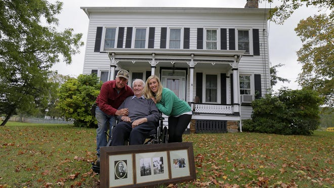 (L-R) Harvey Ort, Jr., Harvey Ort, Sr. and Nicole Ort Moke of Ort Farms, which was settled in 1916 by Harvey Ort, Sr.'s father, Jacob W. Ort, and celebrated their 100th anniversary on Sept. 17, in Long Valley, NJ Wednesday September 28, 2016. They pose with a frame of old family photographs in front of the farmhouse on the property.