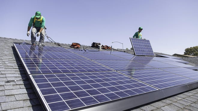 File photo: Workers install solar panels on the roof of a home.