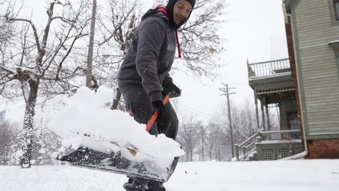 Archie Tharrett, 30, shovels snow for his grandmother, aunt and a couple of neighbors on Sunday in the Woodbridge neighborhood in Detroit.