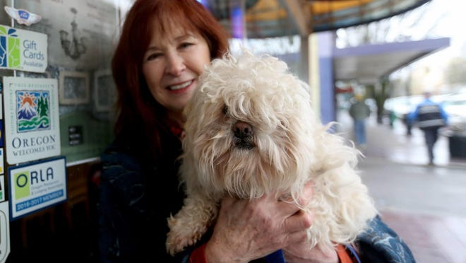 """Pancakes, a poodle mix, is held by Susan Carey, the development director with the Willamette Humane Society, to promote the """"Full Hearts, Empty Kennels"""" event this weekend."""