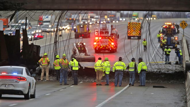 Investigation and cleanup continues at the Rockville Road overpass at I-465, Tuesday, Jan. 10, 2017. A truck carrying a malfunctioning car crusher hit the overpass raining debris down on cars.