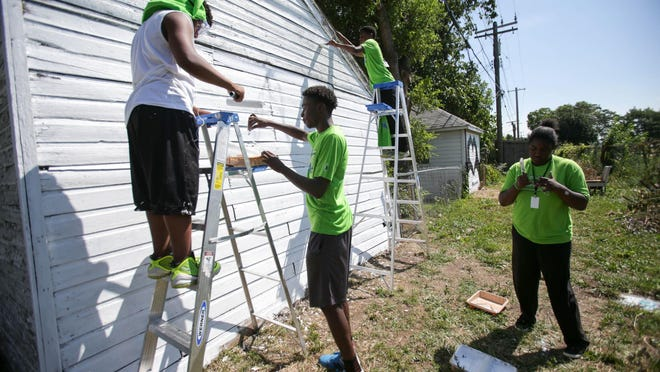 Robert Hardwell, 15; Isaac McKinney, 16; Mikel Hawkins, 15, and Michah Hawkins, 17, all of Detroit, from Grow Detroit's Young Talent summer jobs program, help clean up by painting garages.