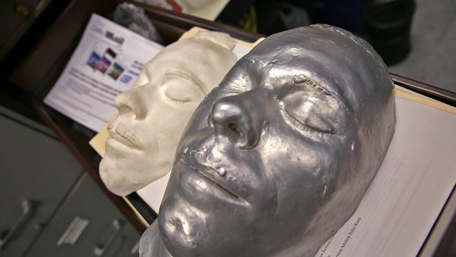 Jo Moore shows items that will be in the Lichtenberger Indianapolis Police History Room, at the IMPD West District headquarters, Thursday, March 23, 2017. She is the archivist and is working to clean, inventory, and catalogue Indianapolis police historic items. These are two John Dillinger death masks that were recovered.