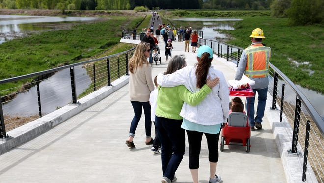 People walk across the Peter Courtney Minto Island Bridge over the Willamette River in Salem. It's one of several places in Salem to get some exercise.