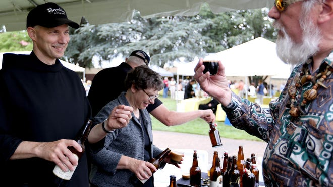Father Martin Grassel, left, gives a beer sample to Dale Small, of Silverton, at the Mount Angel Abbey Saint Benedict Festival in 2015. Just another example of people hating Oregon beer, right?