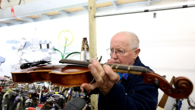"""Bill Thompson examines a broken violin during a Repair Fair in January. """"Fixperts"""" specializing in computers, small appliances, garden tools, bicycles, jewelry, sewing and stringed instruments repaired people's items for free. Another Repair Fair will be 11 a.m. to 1 p.m. Saturday."""