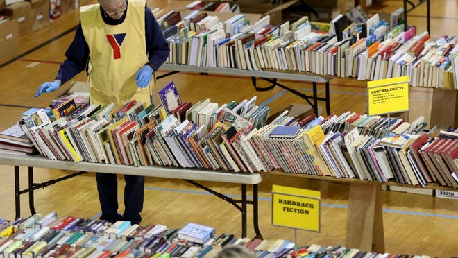 A volunteer sorts through books during last year's YMCA Used Book Sale in Salem. The sale returns 9 a.m. to 6 p.m. March 2-4, with Sunday being $3 sack or $5 box day