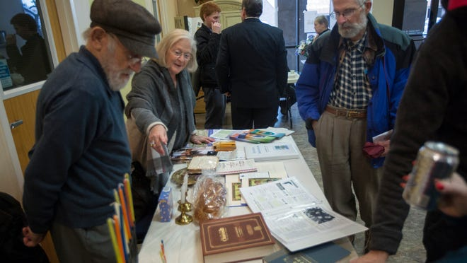 "Sue Prottas, originally of Vancouver, Canada, and now living in Salt Lake City, displays Jewish religious materials to Doug Stark of Holladay, on right, while standing next to her husband Bob Prottas, originally of Seattle, Washington, and now living in Salt Lake City, during the Salt Lake Interfaith Roundtable's ""Generosity of Faith Fair"" open house at the Center for Spiritual Living in South Salt Lake on Monday, Feb. 19, 2018."