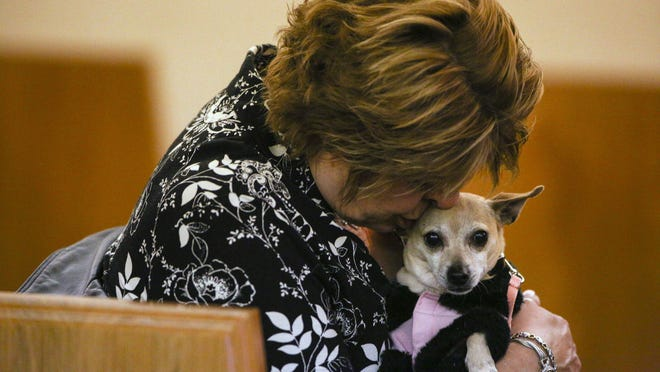 In this Thursday, April 12, 2018, photo, pet owners attend a community memorial service for the 30 dogs that were killed at Storm's Ahead Kennel during at Clock Funeral Home in Muskegon, Mich. Each pet that perished in the March 30 fire has been identified. Public safety officials haven't yet determined what caused the fire, but they ruled out arson. (Mike Krebs/Muskegon Chronicle via AP)