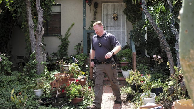 An FBI agent leaves the home of Robert Chain in the Encino section of Los Angeles on Thursday, Aug. 30, 2018.