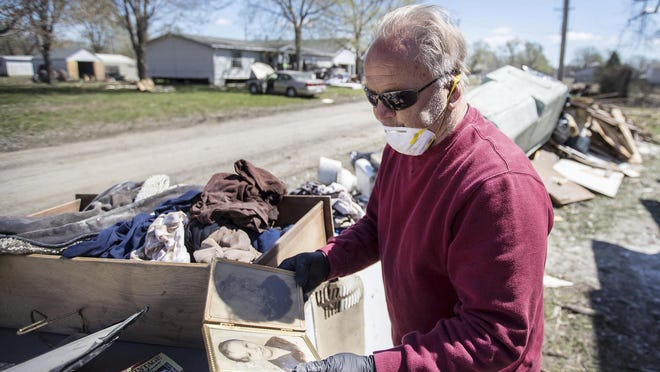 John O'Connor picks up a photo of him and his brother from the 1950s that was pulled out of his flood-damaged home in Pacific Junction, Iowa on Friday, April 19, 2019. The flooding barely damaged his photo but wiped out the photo of his brother. The evacuation order for the Iowa town was just lifted after weeks of flooding.