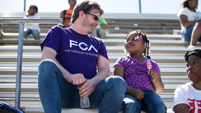 Eric Mayne, FCA Media Relations manager, talks to Cassidy Knight, 5, of Detroit during a community celebration event for FCA's Mack/Jefferson North-area neighbors at Southeastern High School in Detroit on June 7. Fiat Chrysler is readying a community benefit plan to infuse Southeastern with funding for industrial technology education.