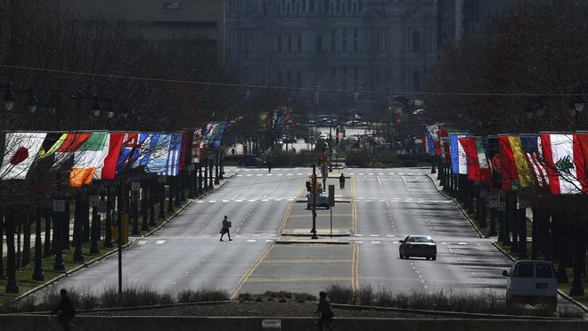 This March 26, 2020 photo shows an empty Benjamin Franklin Parkway in Philadelphia. Gov. Tom Wolf is expanding his order for residents to stay at home in most circumstances to almost one-third of Pennsylvania's counties. The governor's office said Saturday that Wolf was expanding the order to Beaver, Centre and Washington Counties, making a total of 22 of Pennsylvania's 67 counties included. (Tim Tai/The Philadelphia Inquirer via AP)