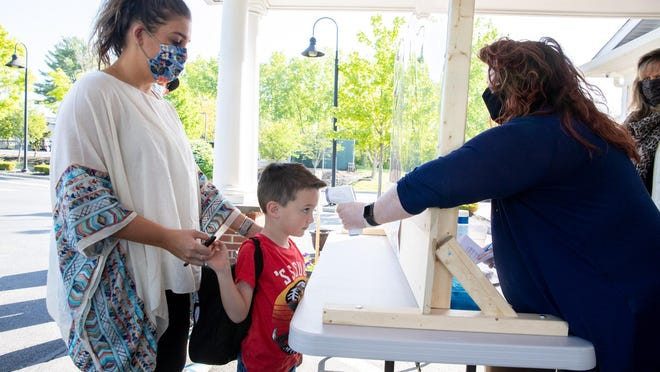 Nicole Frank holds her son Mason's hand as Carla Fratto checks his temperature recently at On My Way Child Care and Early Learning Center in Middletown.