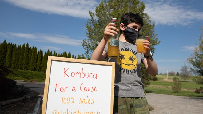 Nine-year-old Shepard Hoffman, 9 holds up his family's home-fermented kombucha in Goshen.  The family says they set up the stand  on May 4, and made $170, which they donated to the charity No Kid Hungry.