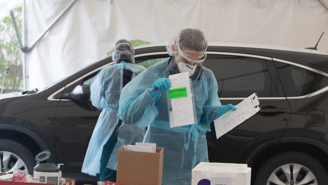 LPN Erin Conley files a COVID-19 swab at Cornerstone Family Healthcare's drive through COVID-19 testing site in Newburgh on May 1.