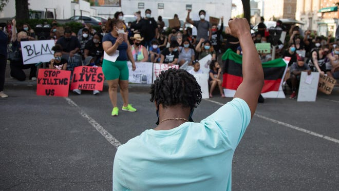 Isiah Valentine raises his  fist in the air in a moment of silence outside of Newburgh's City Hall on June 8, 2020.