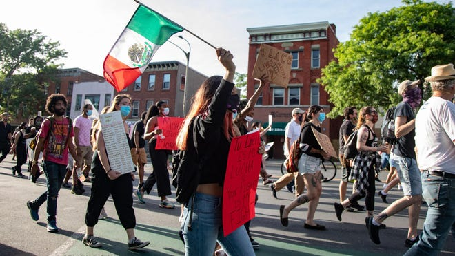 Angela Montiel, 20, of Newburgh, waves a Mexican flag as she marches with protesters down Broadway toward City Hall on Monday evening.