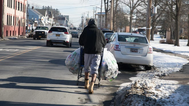 Duke, who currently lives in HONOR's shelter, collects bottles in Middletown on Friday.