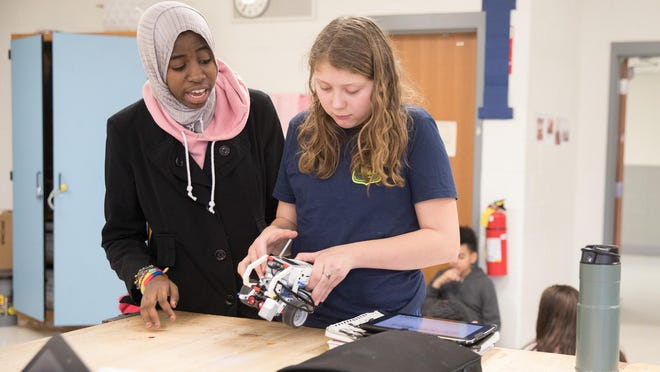 Mariam Bah, left, and Alexandria Gollis work on their robot in Middletown.