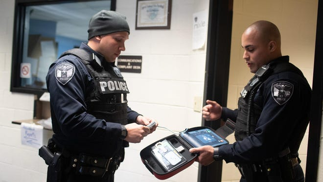 Town of Newburgh police Officers Michael Surita, left, and Matt Zuniga talk Wednesday about reviving unconscious people using CPR and AED defibrillators. The two helped save the life of a crash victim on Sunday.