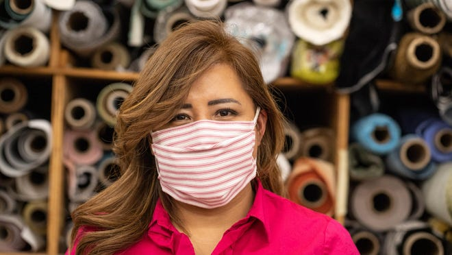 Rocio Silva demonstrates on Monday one of the face masks she is making out of scrap fabric at R. Ramos Upholstery Inc. in Newburgh for hospitals that are running low.