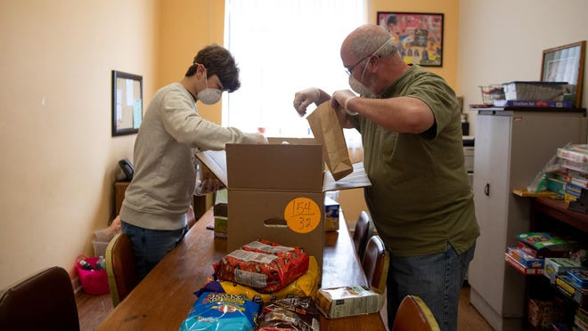Volunteers Sean Miller, left, and his father, Glenn Miller, pack bags of toiletries for families in need in Goshen on Wednesday.