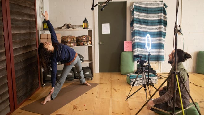 Liz Glover Wilson, left, teaches a yoga class while Billy Schmidt films it at Stone Wave Yoga in Gardiner on Thursday. The videos are put on YouTube.