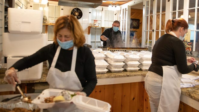 Jeannie Tolp, left, and Tara O'Dell, right, help pack more than 400 lunches while Matt Lare, center, cooks Thursday at the Lazy Pond Bed and Breakfast in Liberty.