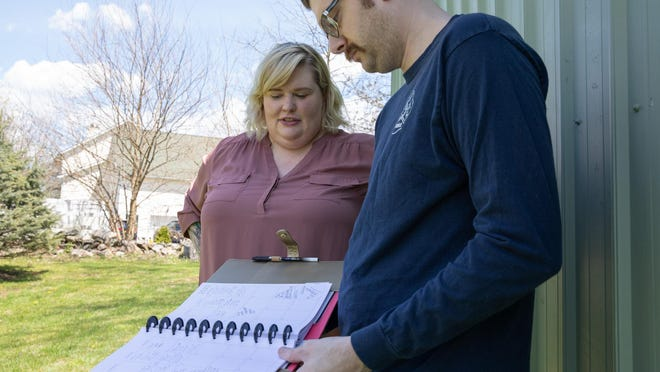 Nicole Miller, left, and her husband, Daniel Bennet, look over a notebook at their home in Montgomery on Saturday. Bennet used the journal to document Miller's experiences after getting sick with COVID-19.