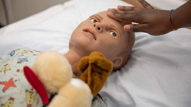 """Nursing student Edna Aboagye interacts on Wednesday with """"Hal,"""" a child-like robot used by SUNY Orange nursing students to simulate caring for a child."""