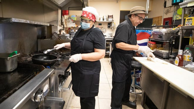 Jackie Perez, left and her husband Heyner Perez, left make food together at Jackie's Latin Kitchen in Middletown on March 30.