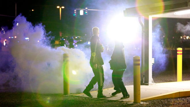 Police officers fire tear gas and use a high-powered spotlight to disperse demonstrators during a protest in Salem.