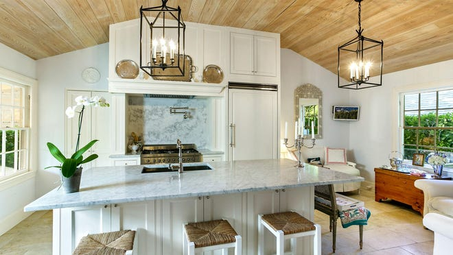 During an extensive renovation, a new kitchen was added to a house built in 1940 at 221 Monterey Road on the North End of Palm Beach. The ceiling was raised and covered in wood to echo the look the original one in the adjacent dining room.