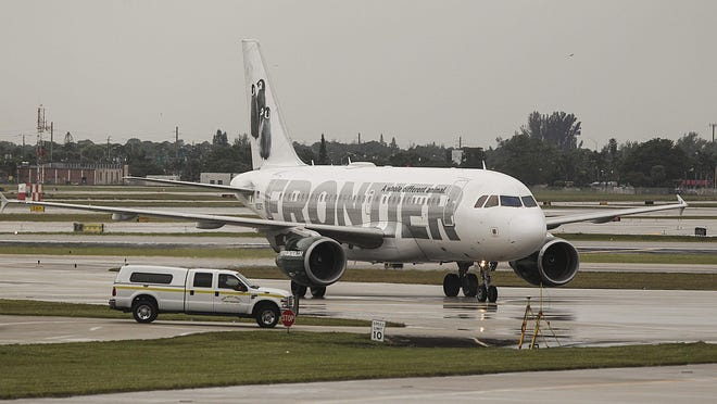 A Frontier jet taxis toward its gate at the Palm Beach International Airport Friday, November 21, 2014 after arriving for the first time from Trenton, NJ just before noon.