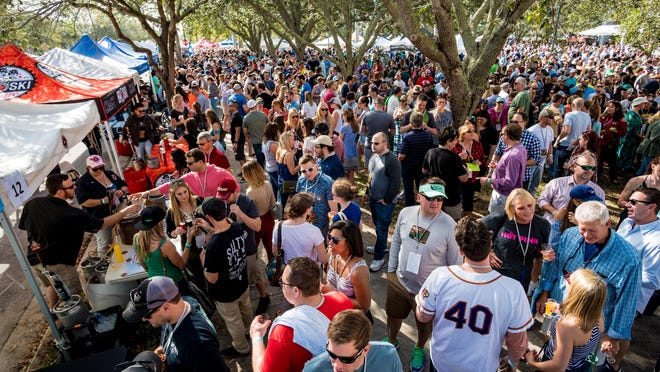 Patrons line up at different vendors during the Jupiter Craft Brewers Festival inside Roger Dean Stadium in Jupiter on Jan. 27, 2018.