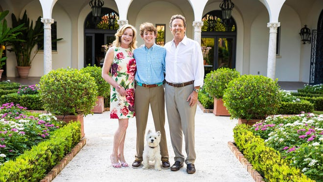 Palm Beachers Frances and Jeff Fisher stand with their son, Harrison, in the courtyard of their restored-and-renovated landmark house built in 1929 in El Bravo Park in Palm Beach's Estate Section.