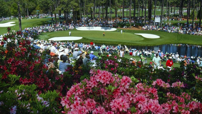 Golf fans watch on the par three 16th hole during a practice round for the Masters at Augusta National Golf Club in Augusta, Ga., last year.